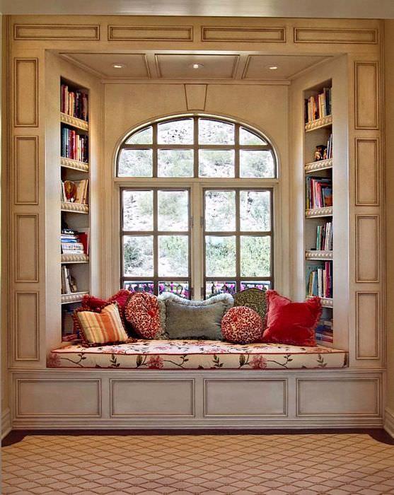 Небольшой диванчик для чтения книг в оконном проеме