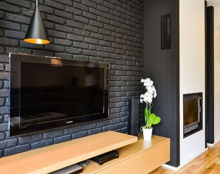 Телевизионная панель на серой кирпичной стене