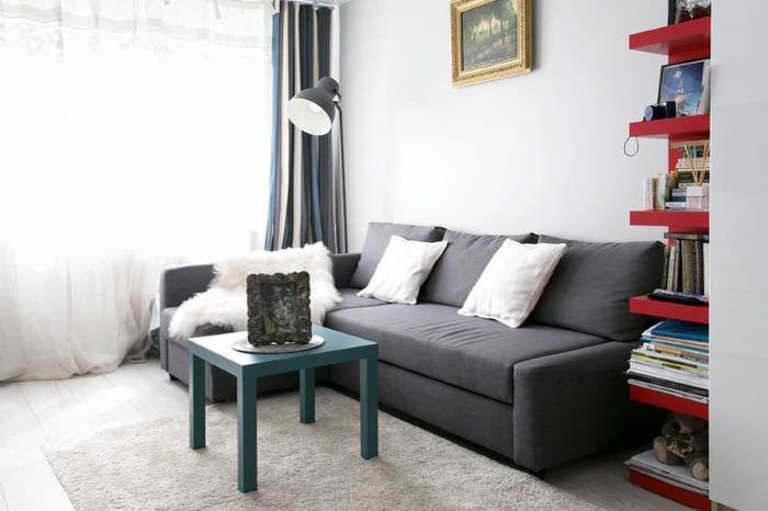 Темно-серый диван в гостиной с большими окнами