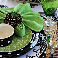 Зеленые салфетки на тарелках с черным орнаментом