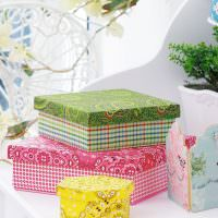 Три красивые коробки на белом комоде