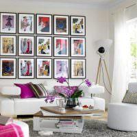 Коллекция картин над белым диваном
