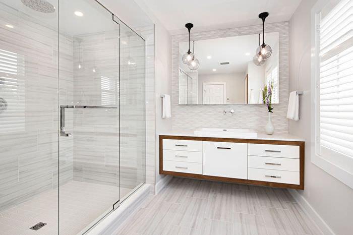 Два подвесных светильника над большим зеркалом в ванной