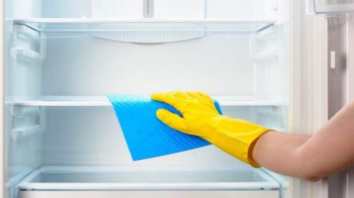 Мытье холодильника тряпкой.