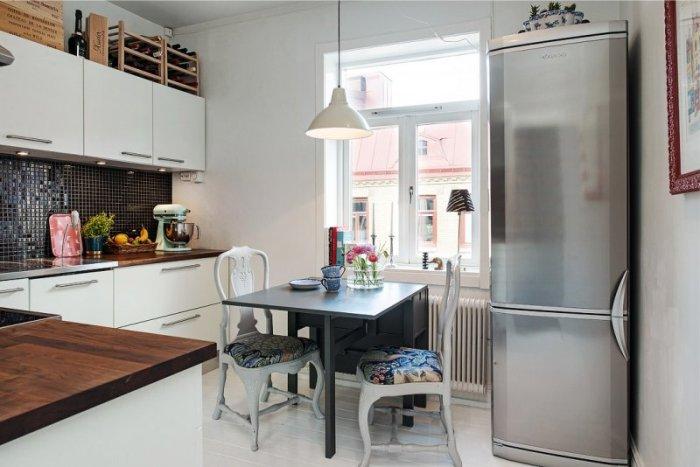 Холодильник на кухне с обеденной зоной.