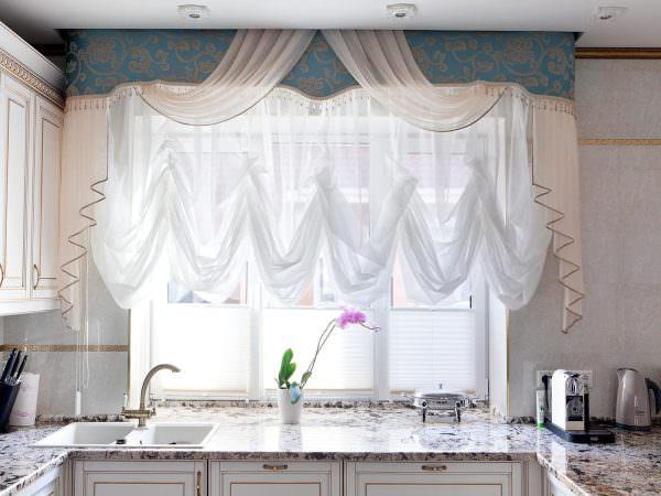 Кухонные ламбрекены выполняют двойную функцию. Они скрывают от сторонних глаз карниз и крепления, а также создают в помещении особый уют.