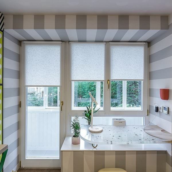 Для кухни с балконной дверью удобны будут рольшторы, французские или классические горизонтальные жалюзи.