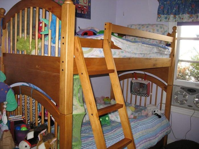 Компактная кровать у окна с двумя ярусами и лестницей