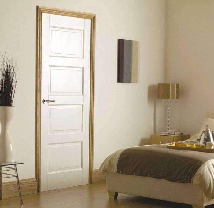 Светлые двери в спальне бежевых цветов с акцентными наличниками
