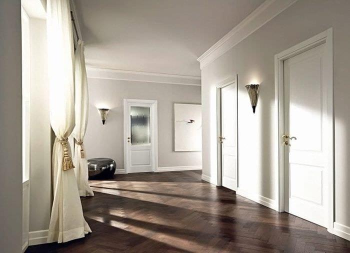 Светлые двери в комбинации с темным ламинатом и светильниками на стенах
