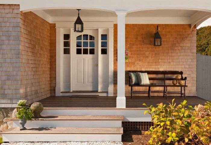 Входная дверь в загородном доме  с отделкой стен сайдингом