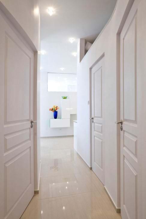 Белые двери в коридоре с глянцевым полом